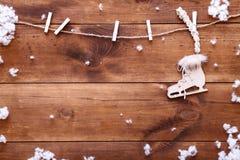 Eislauf auf Winterkonzept, weißer Schlittschuh, der am hölzernen braunen Hintergrund mit Schneeflocken, Draufsicht mit Kopienraum Stockfotos