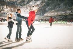 Eislauf der glücklichen Familie im Freien an der Eisbahn Kinder, die abwärts sledding sind Stockbilder