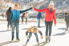Eislauf der glücklichen Familie im Freien an der Eisbahn Kinder, die abwärts sledding sind Stockfotografie
