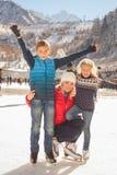 Eislauf der glücklichen Familie im Freien an der Eisbahn Kinder, die abwärts sledding sind Lizenzfreie Stockfotos