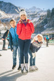 Eislauf der glücklichen Familie im Freien an der Eisbahn Kinder, die abwärts sledding sind Lizenzfreies Stockbild