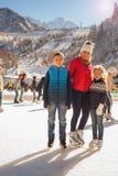 Eislauf der glücklichen Familie im Freien an der Eisbahn Kinder, die abwärts sledding sind Lizenzfreie Stockfotografie