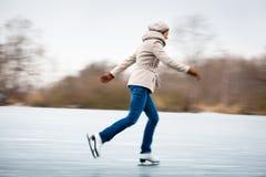 Eislauf der jungen Frau draußen auf einem Teich lizenzfreie stockbilder