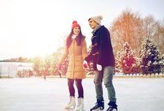 Eislauf des glücklichen Paars auf Eisbahn draußen lizenzfreies stockfoto
