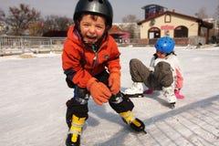 Eislaufenkindspaß auf Schnee Stockfoto