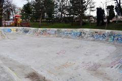 Eislaufrochenpark skatepark Entwurfsskateboard, das leeren Beton mit Graffiti Skateboard fährt stockbilder