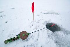Eisloch im Winterfischen und -stange Stockfoto