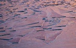 Eisoberfläche auf einem See am Sonnenuntergang Stockfotos