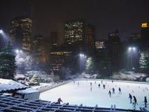 Eisschlittschuhläufer genießen einen winterlichen Central Park unter Schnee, NYC Stockbild