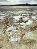 Eisschmelze auf sandigem Strand Detail der Eisscholle mit tiefen Sprüngen nach innen Stockbilder