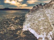 Eisschmelze auf sandigem Strand Detail der Eisscholle mit tiefen Sprüngen nach innen Stockfotos