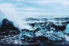 Eisscholle im Ozeanschwarzstrand Stockfotos