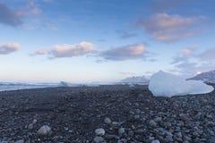 Eiswürfel, der auf schwarzem Felsenstrand mit Hintergrund des blauen Himmels bricht Lizenzfreie Stockfotos