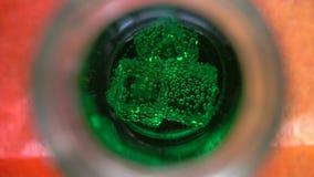 Eiswürfel, die in mit Kohlensäure durchgesetztes grünes Wasser schwimmen stock footage