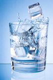 Eiswürfel fallen in Glas Wasser auf blauem Hintergrund Stockfotos