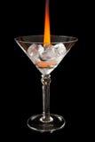 Eiswürfel im Glas mit Flamme auf glänzender schwarzer Oberfläche Lizenzfreies Stockfoto