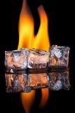 Eiswürfel mit Flamme auf glänzender schwarzer Oberfläche Stockfoto