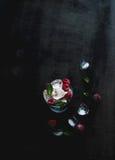 Eiswürfel mit tadellosen Blättern und Himbeere im Glas auf dunklem Schmutz tauchen auf Stockfotografie