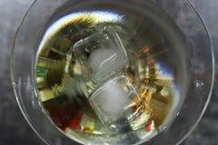 Eiswürfel schließen herauf das Schmelzen im Alkoholglas auf grauem Hintergrund Alkoholisches Stangenkonzept Champagne mit den Fli Lizenzfreies Stockfoto