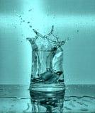 Eisw?rfel, die in Glas Wasser spritzen lizenzfreie stockbilder