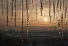 Eiszapfen auf Dach mit schönem Sonnenaufgang Lizenzfreie Stockbilder
