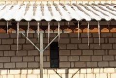 Eiszapfen auf dem Dach des Backsteinhauses Lizenzfreie Stockfotos