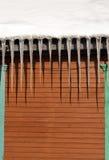 Eiszapfen auf dem Dach des Holzhauses Stockbilder