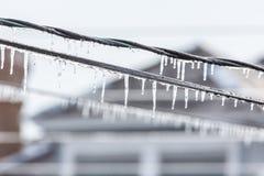 Eiszapfen auf Energiedrähten Stockfoto