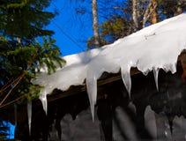 Eiszapfen auf hölzernem Dach Lizenzfreie Stockfotografie