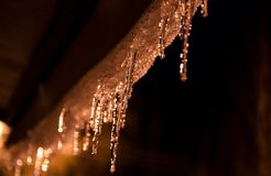 Eiszapfen belichtet durch warmes Straßenlaterne in der Nacht gegen bewölkten Himmel lizenzfreie stockbilder
