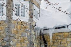 Eiszapfen, die am Dach des Hauses hängen Stockfotografie