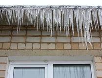 Eiszapfen, die an den Dachgesimsen hängen Stockfotos