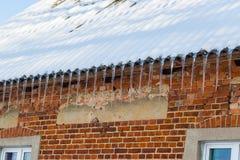 Eiszapfen, die an einem Dach hängen Stockfotos