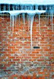 Eiszapfen, die vom Dach des alten Backsteinbaus hängen stockfotos