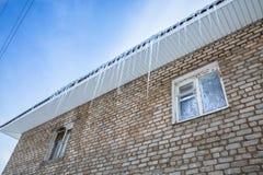 Eiszapfen, die vom Dach des Backsteinbaus hängen Eisige Muster Lizenzfreie Stockfotografie