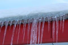 Eiszapfen, die vom Dach des Gebäudes gegen den blauen Himmel hängen Stockbilder