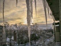 Eiszapfen, die vom Dach eines Wohngebäudes in einem Wohngebiet einer kleinen Winterstadt bedeckt mit Schnee hängen Stockfotografie