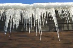 Eiszapfen, die vom Dach hängen Lizenzfreie Stockfotos