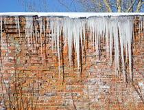 Eiszapfen, die vom Dach hängen Lizenzfreies Stockfoto