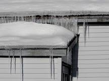 Eiszapfen, die vom Dach hängen Stockbilder