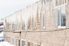 Eiszapfen, die vom Dach hängen Stockbild