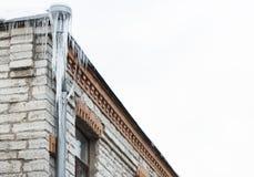 Eiszapfen, die vom Gebäudedach und -abflussrohr hängen Stockbilder