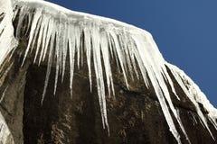 Eiszapfen hängen am Felsen mit blauem Himmel Stockfotos