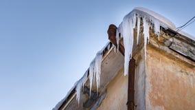 Eiszapfen hängen vom Dach des Gebäudes Gefahr für Passanten, Drohung des Todes und Verletzung von den Eiszapfen Winterdrohungen lizenzfreie stockfotos