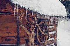Eiszapfen hängen vom Dach eines Holzhauses im Wald nahe der Eberesche stockfoto