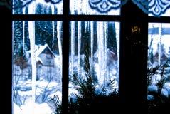 Eiszapfen hinter dem Fenster Stockbilder