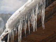 Eiszapfen und Schnee auf dem Dach Stockbild
