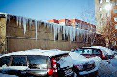 Eiszapfen und schneebedeckte Autos
