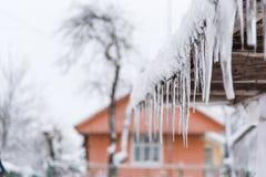Eiszapfenfall auf dem schneebedeckten Dach Gefahr für Passanten, Drohung des Todes und Verletzung von den Eiszapfen lizenzfreie stockfotos