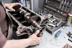 Eixo de manivela do motor, tampa da válvula, pistões Reparador do mecânico no trabalho do reparo da manutenção do motor de automó fotografia de stock royalty free